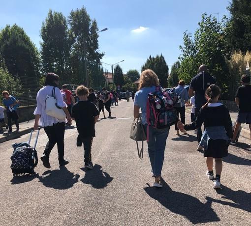 """Genitori e bambini camminano in sicurezza sulle strade che portano a scuola. Effetto delle """"Zone scolastiche"""""""